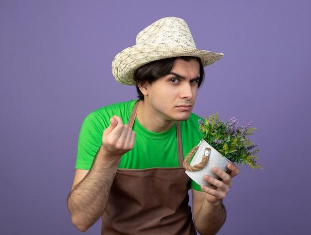 Jovem jardineiro suspeito de uniforme, usando chapéu de jardinagem, segurando uma flor em um vaso de flores, mostrando um gesto de dinheiro