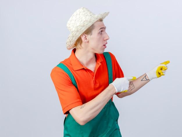 Jovem jardineiro usando macacão e chapéu em luvas de borracha apontando com o dedo indicador para o lado