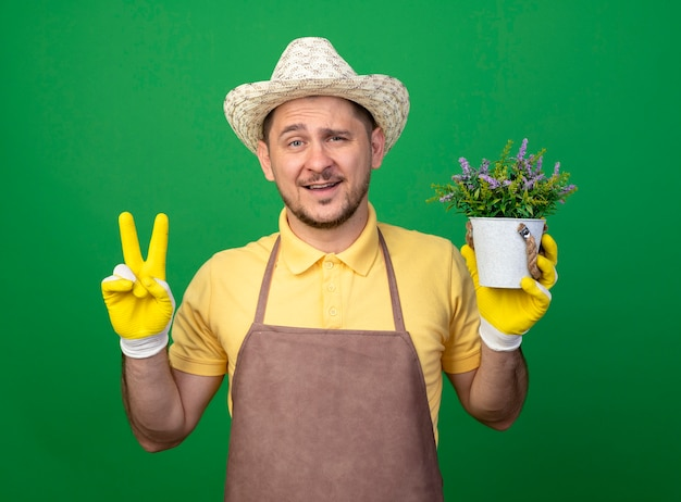 Jovem jardineiro usando macacão e chapéu em luvas de trabalho segurando um vaso de planta em pé sobre uma parede verde