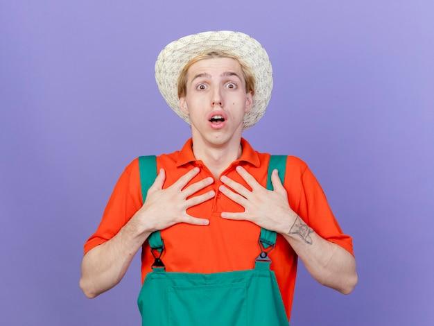 Jovem jardineiro vestindo macacão e chapéu apontando para si mesmo parecendo surpreso