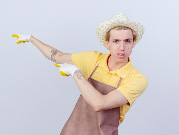 Jovem jardineiro vestindo macacão e chapéu com luvas de borracha apontando com o dedo indicador para algo com uma cara séria