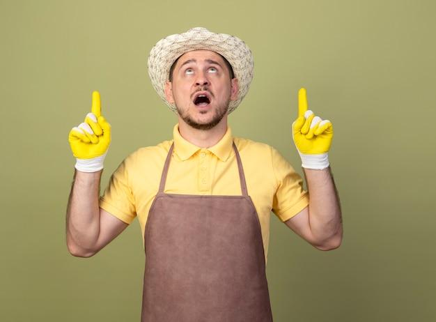 Jovem jardineiro vestindo macacão e chapéu em luvas de trabalho apontando com o dedo indicador para cima parecendo surpreso