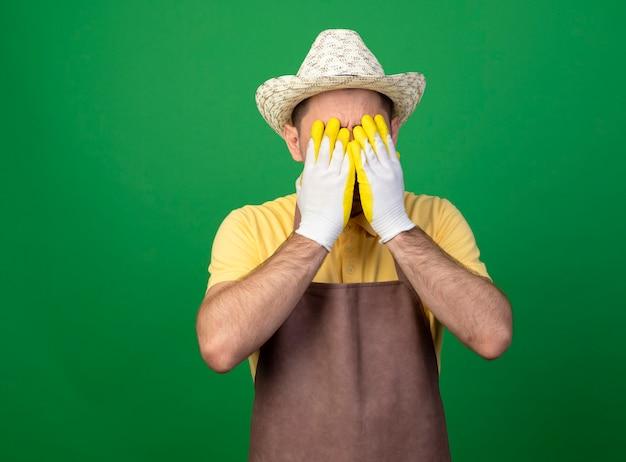 Jovem jardineiro vestindo macacão e chapéu em luvas de trabalho, cobrindo o rosto com as mãos