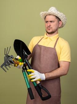 Jovem jardineiro vestindo macacão e chapéu em luvas de trabalho segurando equipamentos de jardinagem olhando para eles não gostando