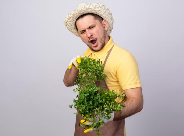 Jovem jardineiro vestindo macacão e chapéu em luvas de trabalho segurando ervas frescas feliz e animado