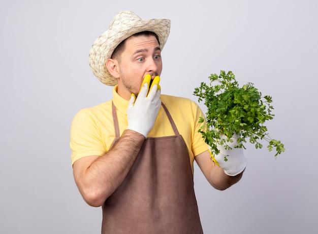 Jovem jardineiro vestindo macacão e chapéu em luvas de trabalho segurando ervas frescas lookign com ervas sendo espantado e surpreso cobrindo a boca com as mãos