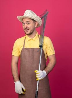 Jovem jardineiro vestindo macacão e chapéu em luvas de trabalho segurando o ancinho sorrindo com uma cara feliz