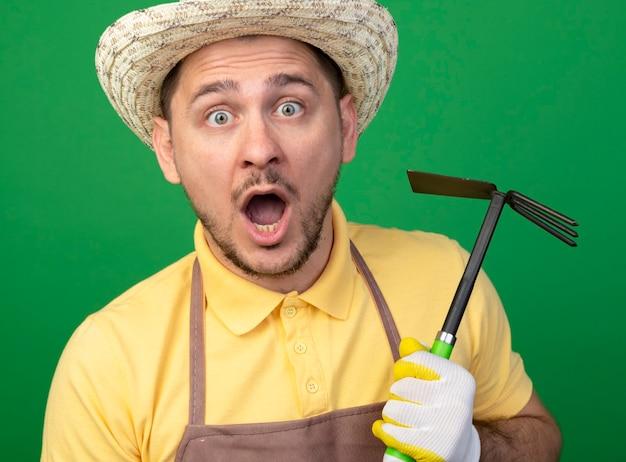 Jovem jardineiro vestindo macacão e chapéu em luvas de trabalho segurando picareta espantado e surpreso