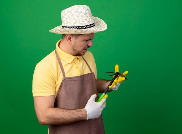 Jovem jardineiro vestindo macacão e chapéu em luvas de trabalho segurando picareta olhando para ela com uma cara séria
