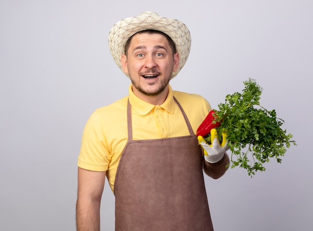 Jovem jardineiro vestindo macacão e chapéu em luvas de trabalho segurando pimentões vermelhos e ervas frescas sorrindo sorrindo