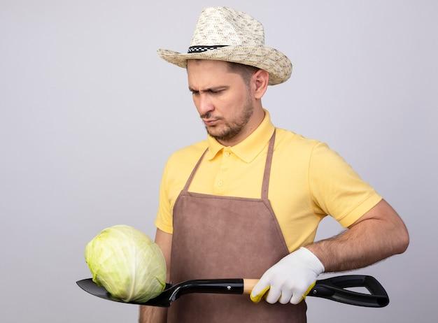 Jovem jardineiro vestindo macacão e chapéu em luvas de trabalho segurando repolho na pá e olhando com cara séria