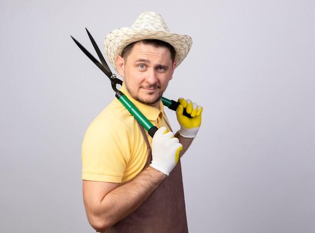 Jovem jardineiro vestindo macacão e chapéu em luvas de trabalho segurando um corta-sebes com um sorriso no rosto