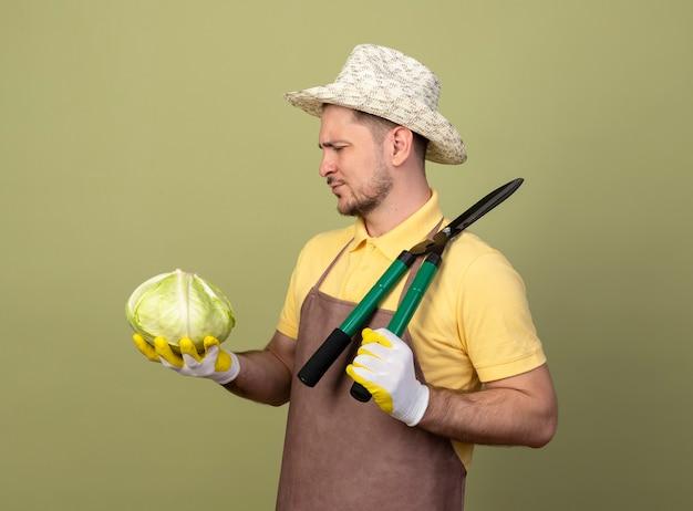 Jovem jardineiro vestindo macacão e chapéu em luvas de trabalho segurando um cortador de cerca viva e repolho olhando para ele com uma cara séria