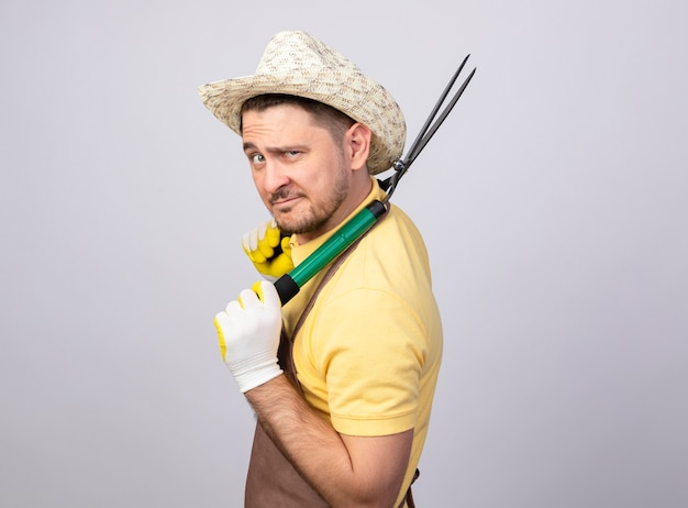 Jovem jardineiro vestindo macacão e chapéu em luvas de trabalho segurando um cortador de cerca viva olhando para a câmera sorrindo confiante