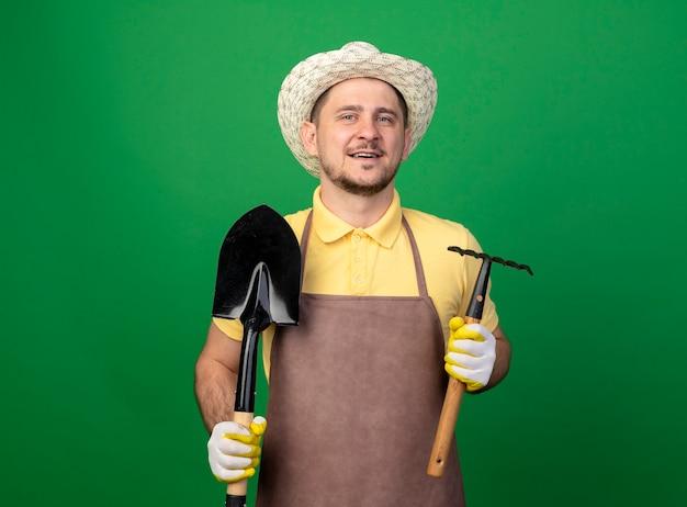 Jovem jardineiro vestindo macacão e chapéu em luvas de trabalho segurando um mini ancinho e uma pá olhando para frente sorrindo com uma cara feliz em pé sobre a parede verde