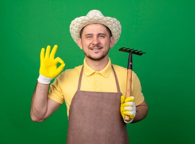 Jovem jardineiro vestindo macacão e chapéu em luvas de trabalho segurando um mini ancinho olhando para frente sorrindo mostrando uma placa de ok em pé sobre a parede verde Foto gratuita