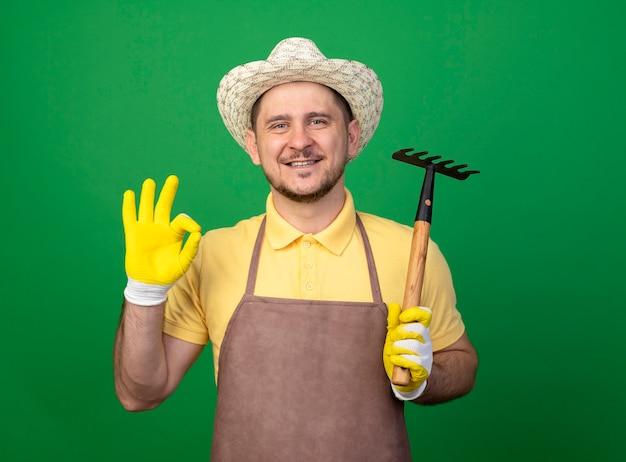 Jovem jardineiro vestindo macacão e chapéu em luvas de trabalho segurando um mini ancinho olhando para frente sorrindo mostrando uma placa de ok em pé sobre a parede verde