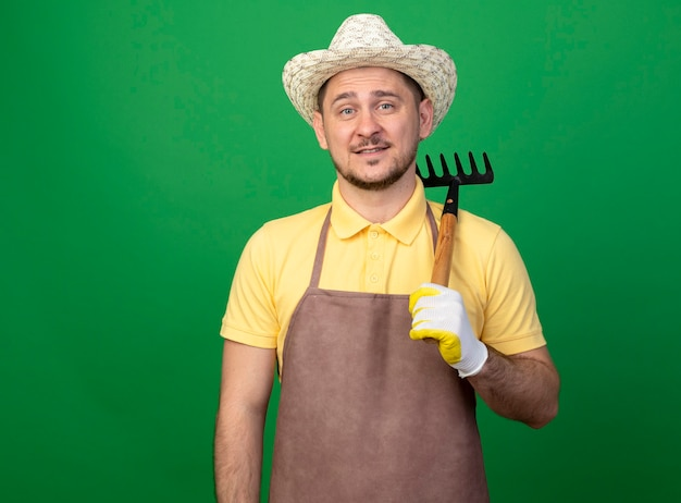 Jovem jardineiro vestindo macacão e chapéu em luvas de trabalho segurando um mini ancinho sorrindo alegremente