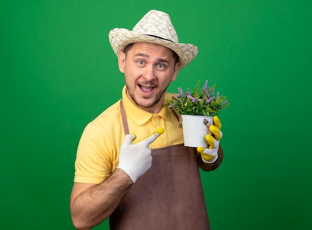 Jovem jardineiro vestindo macacão e chapéu em luvas de trabalho segurando um vaso de planta apontando com o dedo indicador para ele sorrindo alegremente em pé sobre a parede verde