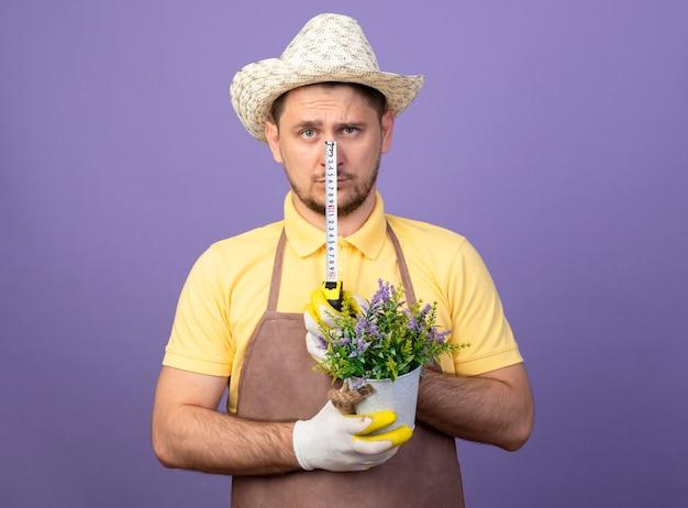 Jovem jardineiro vestindo macacão e chapéu em luvas de trabalho segurando um vaso de planta e fita métrica, olhando para frente com uma cara séria em pé sobre a parede roxa