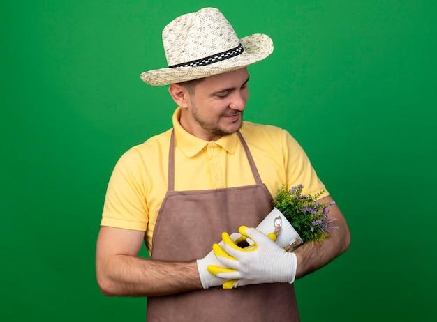 Jovem jardineiro vestindo macacão e chapéu em luvas de trabalho segurando um vaso de planta olhando para ele com amor e sorrindo em pé sobre a parede verde