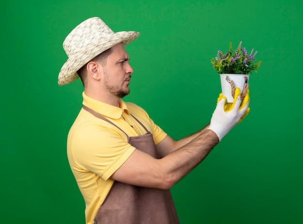Jovem jardineiro vestindo macacão e chapéu em luvas de trabalho segurando um vaso de planta olhando para ele com uma cara séria em pé sobre a parede verde
