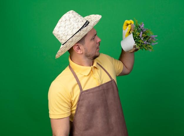 Jovem jardineiro vestindo macacão e chapéu em luvas de trabalho segurando um vaso de planta olhando para ele confuso em pé sobre a parede verde