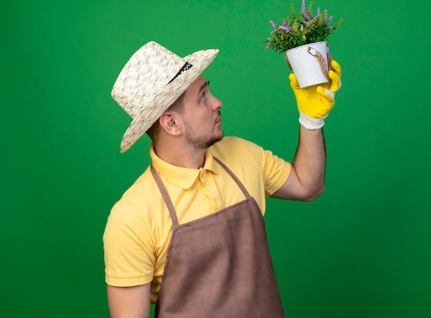 Jovem jardineiro vestindo macacão e chapéu em luvas de trabalho segurando um vaso de planta olhando para ele intrigado em pé sobre a parede verde