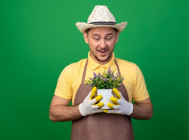 Jovem jardineiro vestindo macacão e chapéu em luvas de trabalho segurando um vaso de planta olhando para ele sendo surpreendido em pé sobre a parede verde