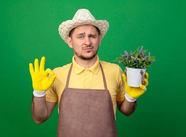 Jovem jardineiro vestindo macacão e chapéu em luvas de trabalho segurando um vaso de planta, olhando para frente com expressão confiante, mostrando a placa de ok em pé sobre a parede verde