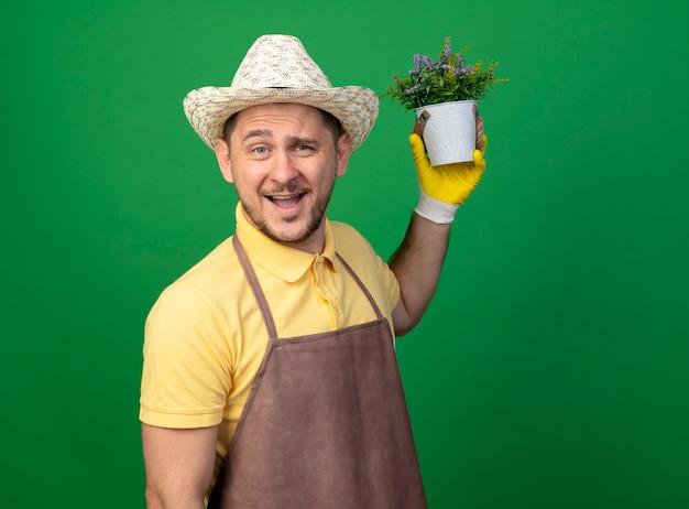 Jovem jardineiro vestindo macacão e chapéu em luvas de trabalho segurando um vaso de planta olhando para frente sorrindo com uma cara feliz em pé sobre a parede verde
