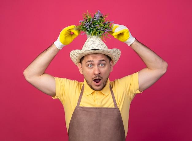 Jovem jardineiro vestindo macacão e chapéu em luvas de trabalho, segurando um vaso de plantas na cabeça, parecendo surpreso e surpreso em pé sobre a parede rosa