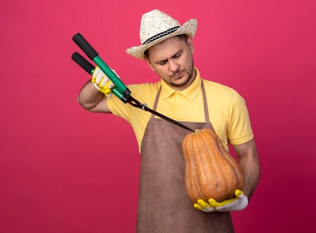 Jovem jardineiro vestindo macacão e chapéu em luvas de trabalho segurando uma abóbora e vai cortá-la usando um corta-sebes em pé sobre a parede rosa