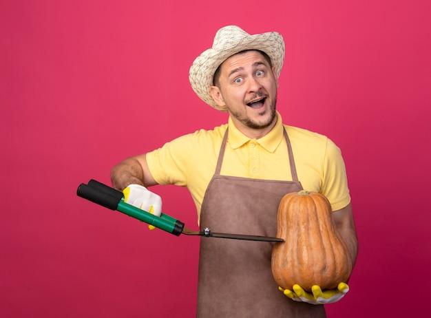 Jovem jardineiro vestindo macacão e chapéu em luvas de trabalho segurando uma abóbora e vai cortá-la usando um corta-sebes feliz e positivo em pé sobre a parede rosa