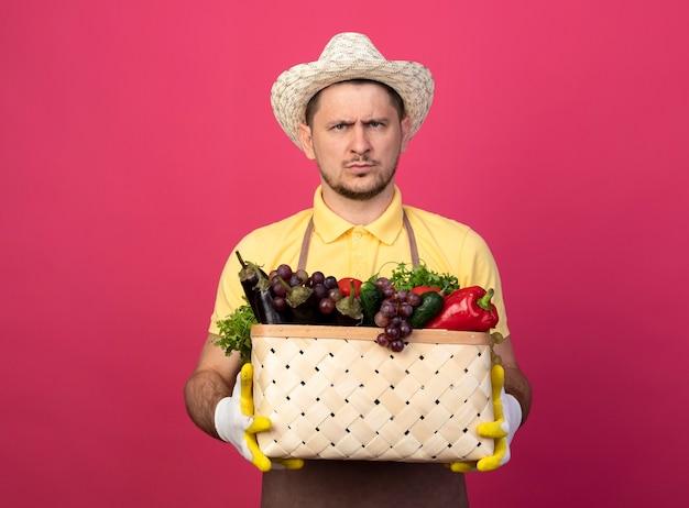 Jovem jardineiro vestindo macacão e chapéu em luvas de trabalho segurando uma caixa cheia de legumes com cara carrancuda e insatisfeito