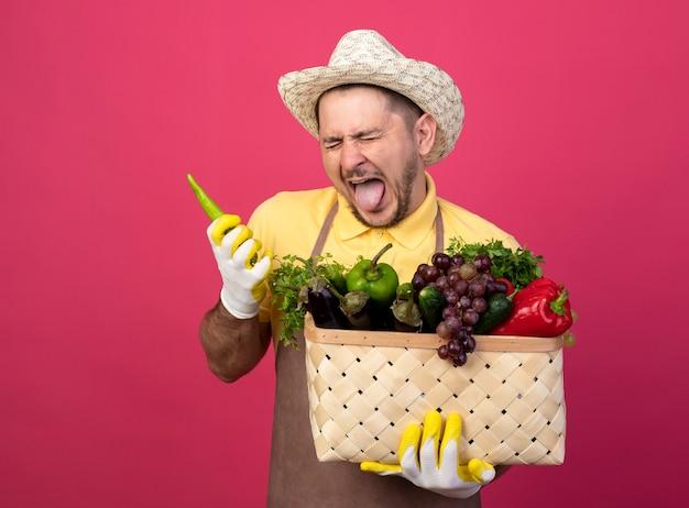 Jovem jardineiro vestindo macacão e chapéu em luvas de trabalho segurando uma caixa cheia de vegetais com pimenta verde esticando a língua com expressão de nojo