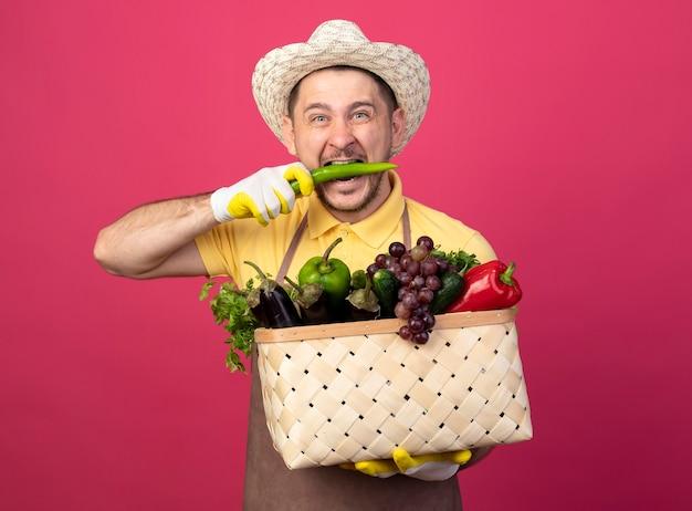 Jovem jardineiro vestindo macacão e chapéu em luvas de trabalho segurando uma caixa cheia de vegetais e mordendo pimenta verde em pé sobre a parede rosa