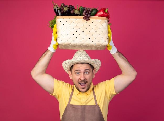Jovem jardineiro vestindo macacão e chapéu em luvas de trabalho segurando uma caixa cheia de vegetais na cabeça, feliz e animado, sorrindo