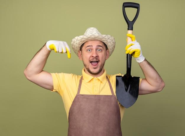 Jovem jardineiro vestindo macacão e chapéu em luvas de trabalho segurando uma pá apontando para baixo e sorrindo alegremente