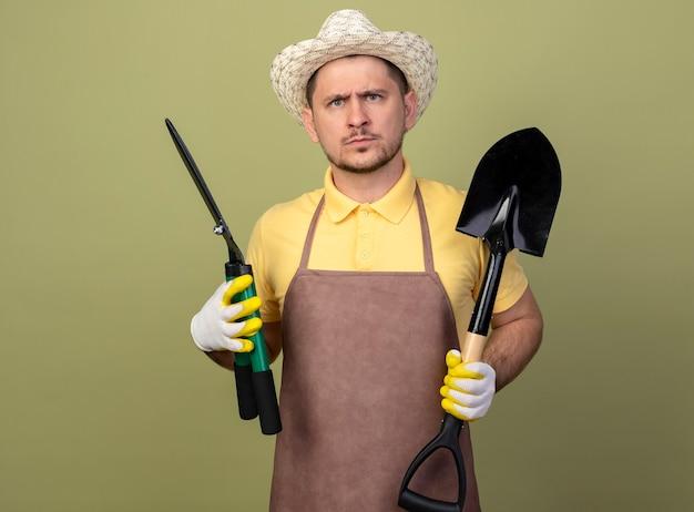 Jovem jardineiro vestindo macacão e chapéu em luvas de trabalho segurando uma pá e um cortador de cerca viva com uma expressão séria