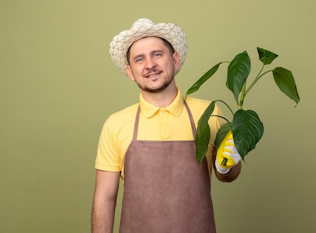 Jovem jardineiro vestindo macacão e chapéu em luvas de trabalho segurando uma planta com um sorriso no rosto