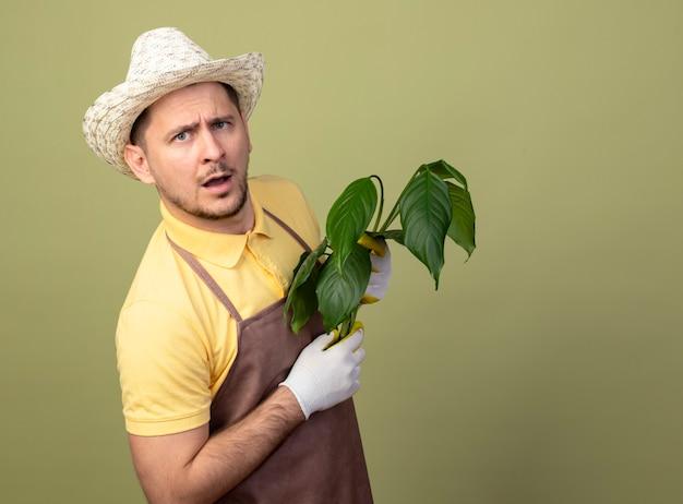 Jovem jardineiro vestindo macacão e chapéu em luvas de trabalho segurando uma planta com uma cara séria