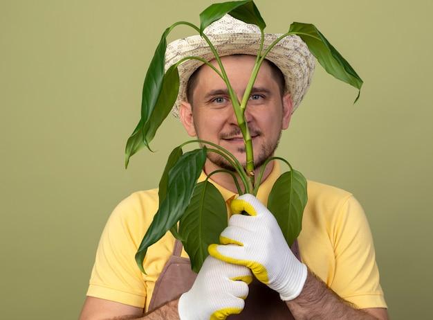 Jovem jardineiro vestindo macacão e chapéu em luvas de trabalho segurando uma planta olhando para a frente sorrindo com uma cara feliz em pé sobre a parede de luz