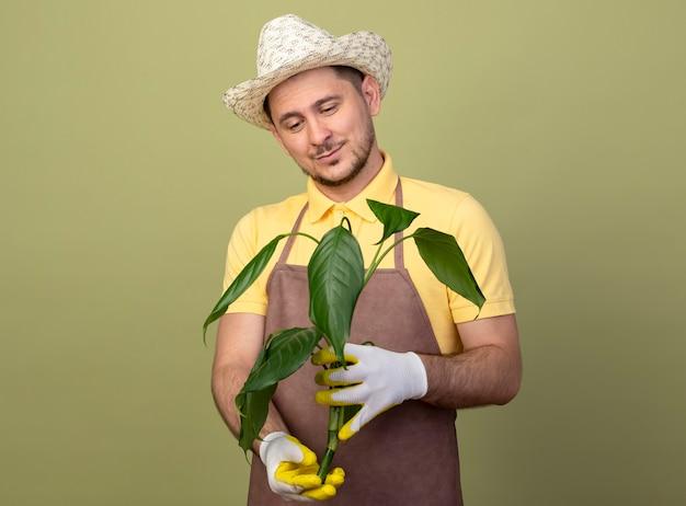 Jovem jardineiro vestindo macacão e chapéu em luvas de trabalho segurando uma planta olhando para ela com um sorriso no rosto