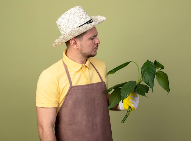 Jovem jardineiro vestindo macacão e chapéu em luvas de trabalho segurando uma planta olhando para ela com uma cara séria