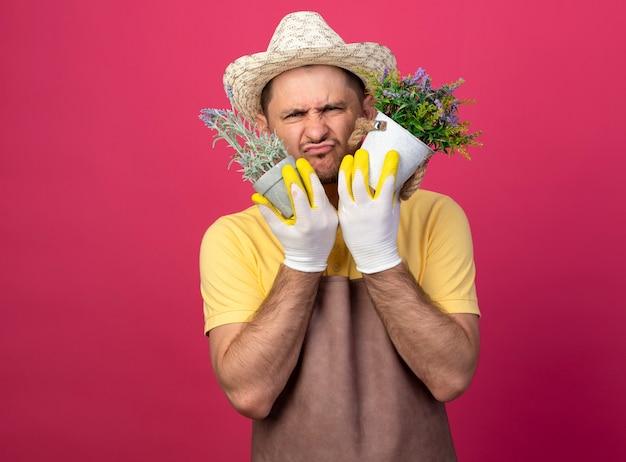 Jovem jardineiro vestindo macacão e chapéu em luvas de trabalho segurando vasos de plantas, confuso e descontente