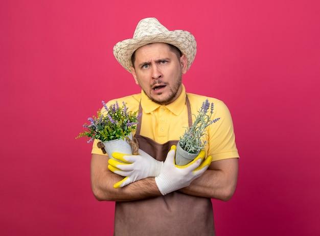 Jovem jardineiro vestindo macacão e chapéu em luvas de trabalho segurando vasos de plantas confuso