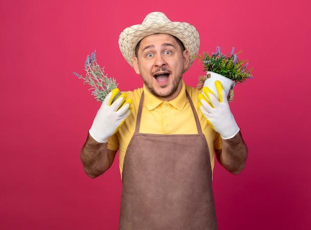 Jovem jardineiro vestindo macacão e chapéu em luvas de trabalho segurando vasos de plantas feliz e alegre