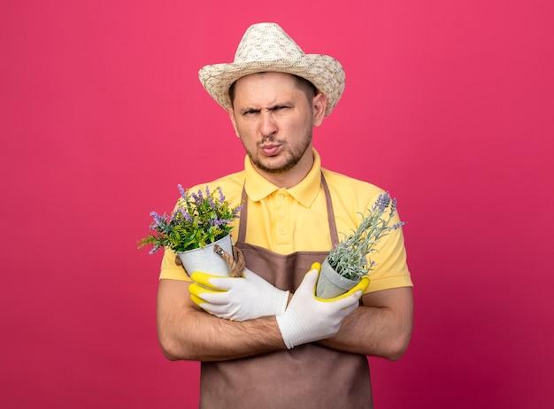 Jovem jardineiro vestindo macacão e chapéu em luvas de trabalho segurando vasos de plantas olhando para a frente com rosto sério e carrancudo em pé sobre a parede rosa