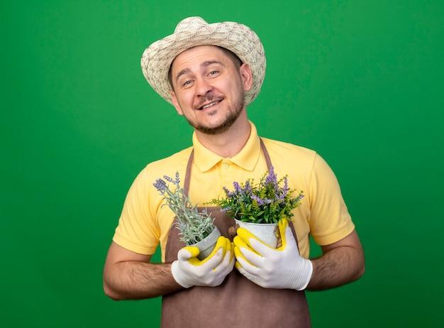 Jovem jardineiro vestindo macacão e chapéu em luvas de trabalho segurando vasos de plantas olhando para a frente sorrindo alegremente em pé sobre a parede verde